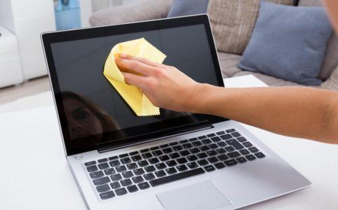 Mujer limpiando computadora portátil